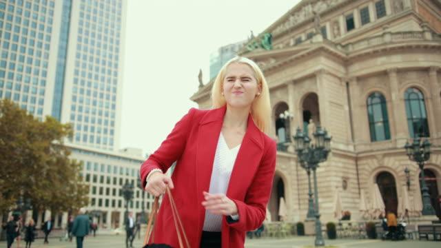 vídeos de stock, filmes e b-roll de linda mulher loira de jaqueta vermelha pega bolsa grande pesada - pesado peso