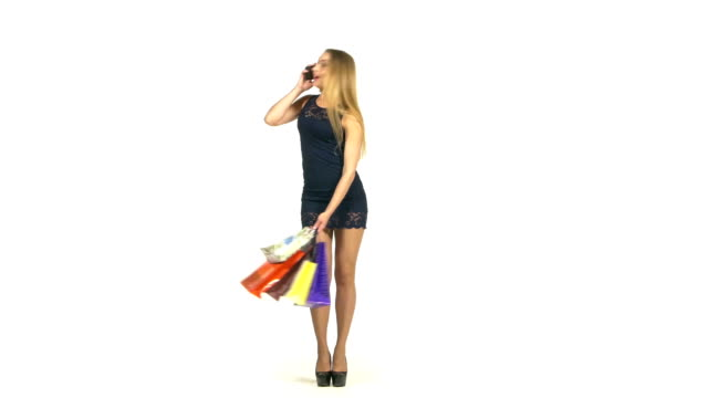 Beautiful blonde woman in short dark blue dress walking with shopping bags talking on the phone on white background video