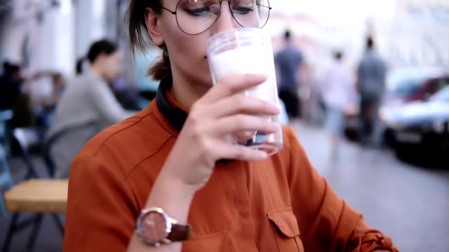 güzel sarışın kadın yaz kafede memnuniyetle içecek köpük iç. kadın ziyaretçi açık havada kadehi kapuçino yudum alarak sahiptir. sokak cafe - tüketime hazır stok videoları ve detay görüntü çekimi