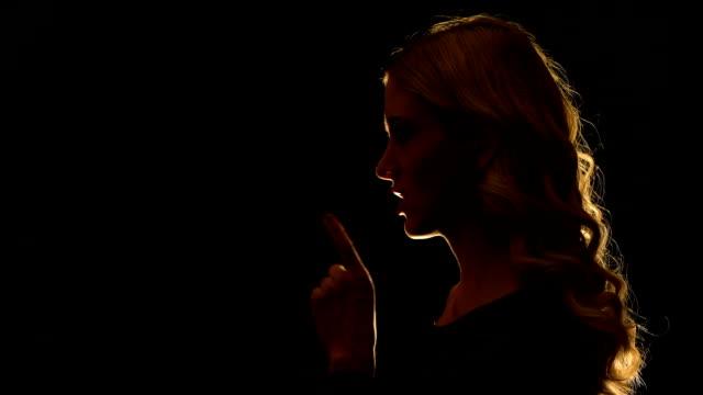 vídeos y material grabado en eventos de stock de hermosa mujer rubia mostrando signo de silencio, misterioso secreto, vista lateral - dedo sobre labios