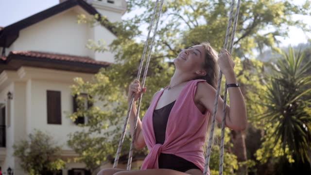 beautiful blonde woman swinging - oscillare video stock e b–roll