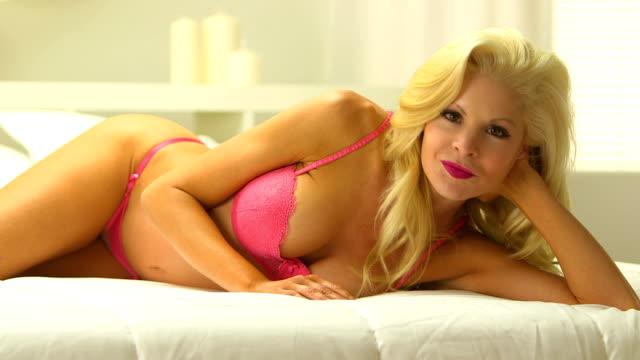 Beautiful blonde woman wearing pink lingerie in bed video