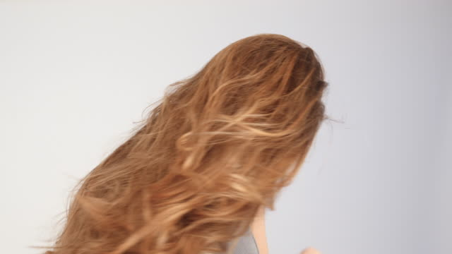 beautiful blonde woman with long hair playing with her hair with wind 03 - video