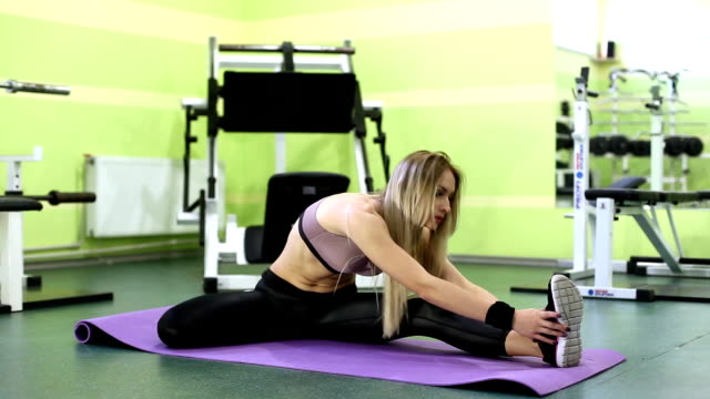 beautiful blonde young woman warming up before training in a  gym. - donna forzuta video stock e b–roll