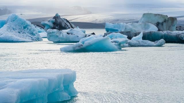 bellissimo ghiaccio blu nella laguna glaciale di jokulsarlon in islanda con vatnajokull, il ghiacciaio più grande d'europa sullo sfondo - ghiaccio galleggiante video stock e b–roll