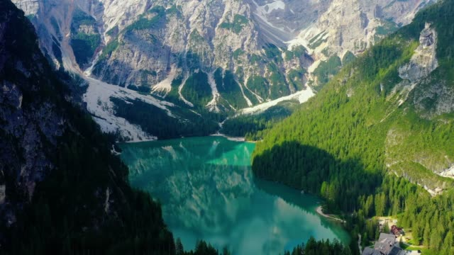 Beautiful blue lake, with the reflection of sunlight in the water. Landscape with forest and mountain around the lake in aerial view with a drone 4K