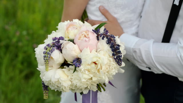 Beautiful bouquet of different colors in the hands of the bride in a white dress. Happy married couple with a wedding flowers. video