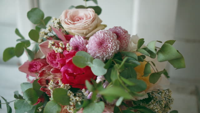 Beautiful bouquet of peonies and roses is on windowsill. Wind is blowing flowers