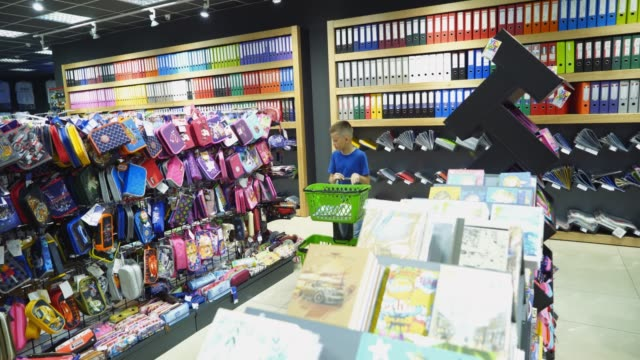 beautiful boy choosing school stationery at a supermarket. - school supplies stock videos and b-roll footage