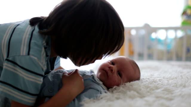 美しい少年は、優しさで抱いて気に自宅に彼の生まれたばかりの赤ちゃんの弟。家族愛幸せコンセプト - 兄弟姉妹点の映像素材/bロール