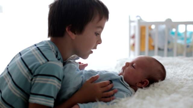 vídeos y material grabado en eventos de stock de muchacho hermoso, abrazando con ternura y cuidado de su hermano recién nacido en casa. concepto de felicidad de amor familiar - hermano