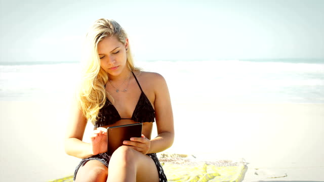 Beautiful Brazilian woman using technology on a beach in Brazil video