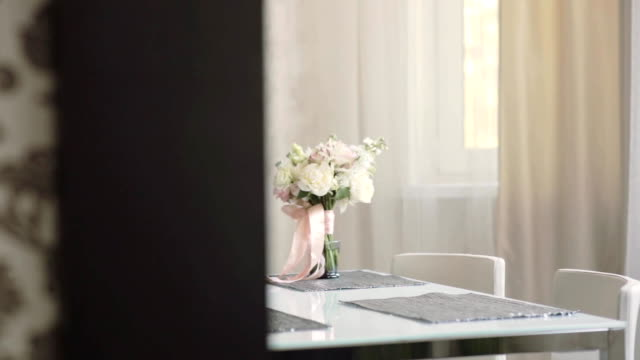 Beautiful bridal bouquet on the table in the morning. Wedding preparations before ceremony. Slider right video