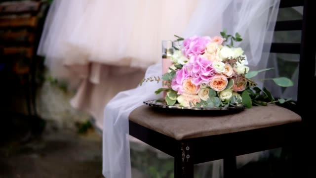 Beautiful bridal bouquet on the table with beautiful wedding dress and bridal accessories on the background. Wedding dress on shoulders, before ceremony. Beautiful wedding bouquet and dress for bride video