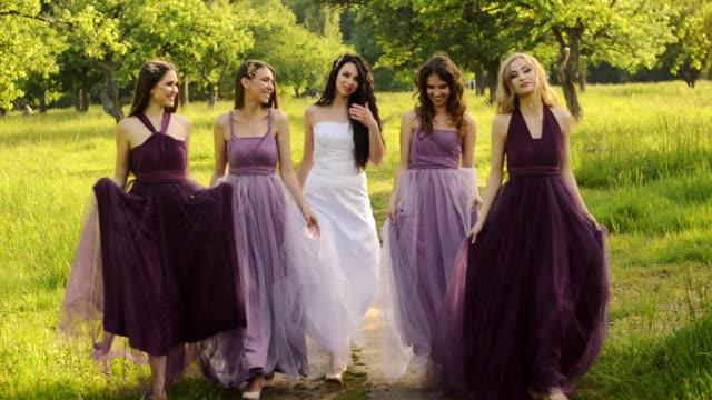 Noiva linda e bridemaids em roxo veste-se de caminhar no parque ou jardim de mãos dadas e rindo à noite. - vídeo