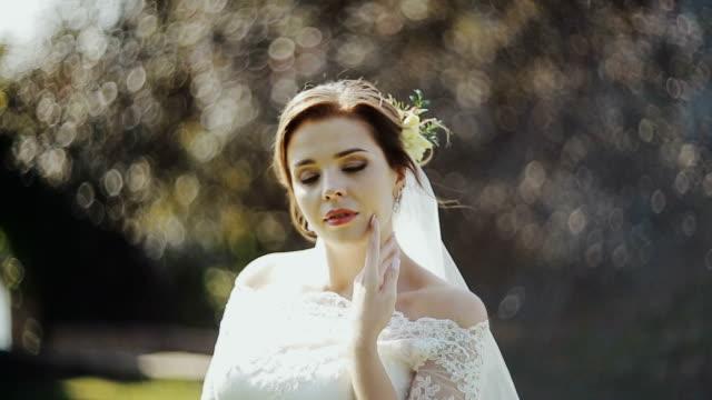 Novia hermosa con vestido elegante mirando a cámara y sonriendo. - vídeo