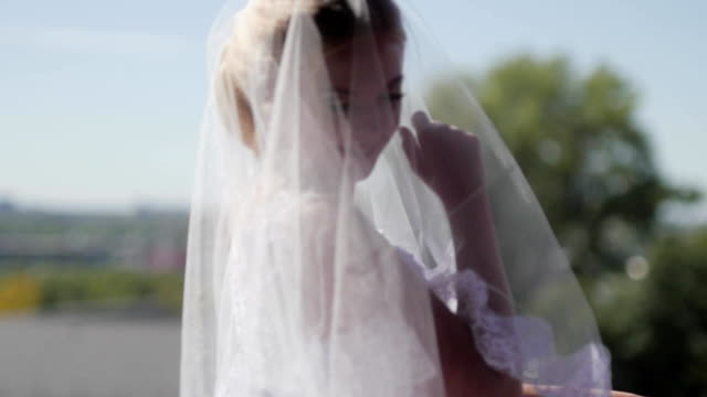 beautiful bride in veil posing near window. slow motion video