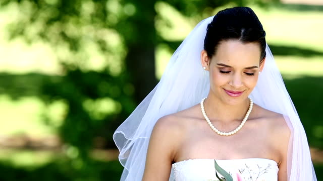 Beautiful bride smiling at camera in the park video