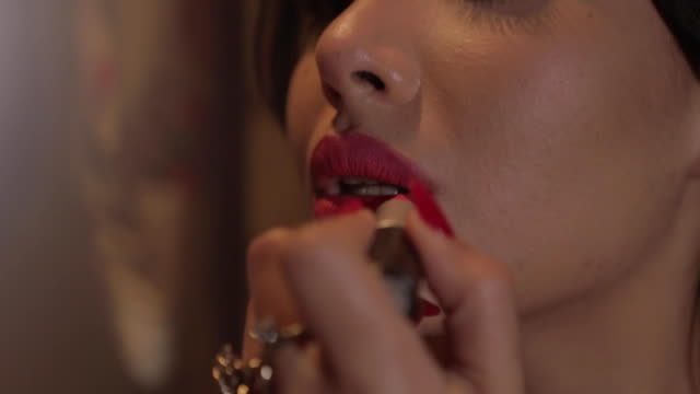Beautiful brunette Arab woman putting on lipstick, holding a vintage mirror and wearing a retro red floral dress. Hotel room in Paris with Sun light flare. Close Up Make Up. Beautiful brunette Arab woman putting on lipstick, holding a vintage mirror and wearing a retro red floral dress. Hotel room in Paris with Sun light flare. Close Up Make Up. lipstick stock videos & royalty-free footage