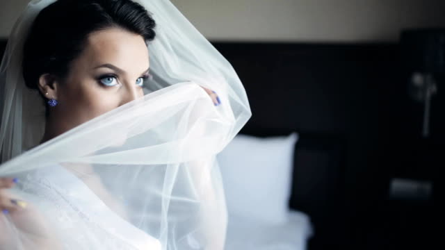 Beautiful brunette bride posing to photographer. Woman smiling, hides behind a veil. Female with beautiful make-up video