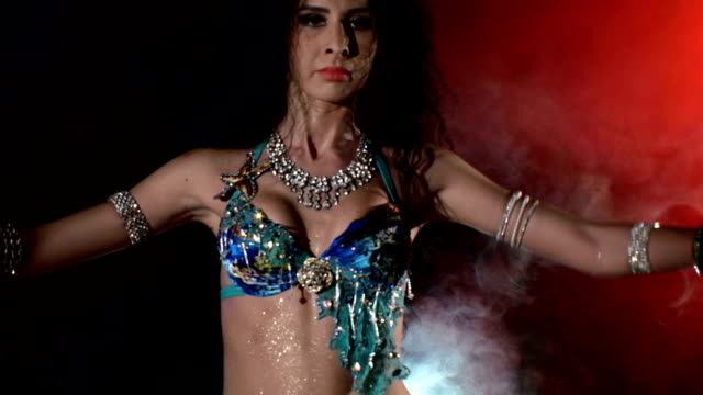 beautiful brunette dancing belly dance, on black, back light, cam moves upwards - belly dancing stock videos and b-roll footage