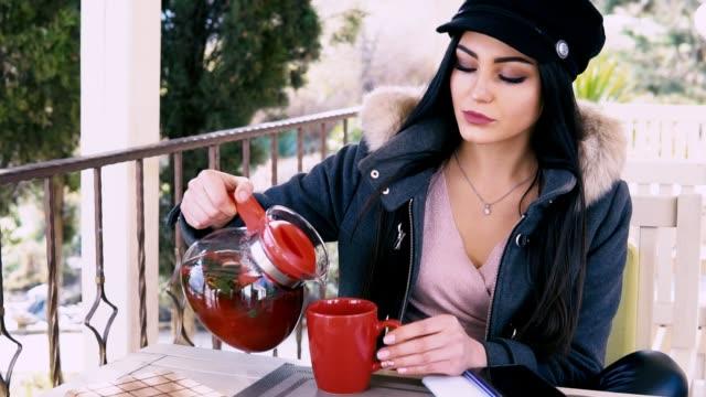 beautiful brunette drinking hot tea in the street restaurant video