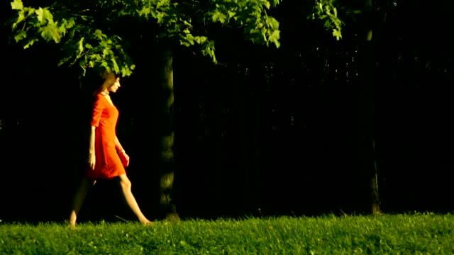 sol sağ, profil görünümü parkta çim yürüyüş kırmızı elbise güzel esmer kız. yavaş hareket videosu - uzun adımlarla yürümek stok videoları ve detay görüntü çekimi