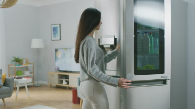 Beautiful Brunette Girl in White Jeans and Grey Sweater Comes to the High-Tech Fridge with a Glass Door and Takes a Green Apple. She goes to the Living Room. Flat has Modern Interior. Beautiful Brunette Girl in White Jeans and Grey Sweater Comes to the High-Tech Fridge with a Glass Door and Takes a Green Apple. She goes to the Living Room. Flat has Modern Interior. Shot on RED EPIC-W 8K Helium Cinema Camera. freezer stock videos & royalty-free footage