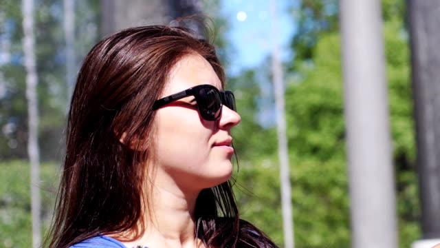 vidéos et rushes de belle femme heureuse brune à lunettes de soleil appréciant le sourire du soleil nature au ralenti. 1920 x 1080 - rouge à lèvres rouge
