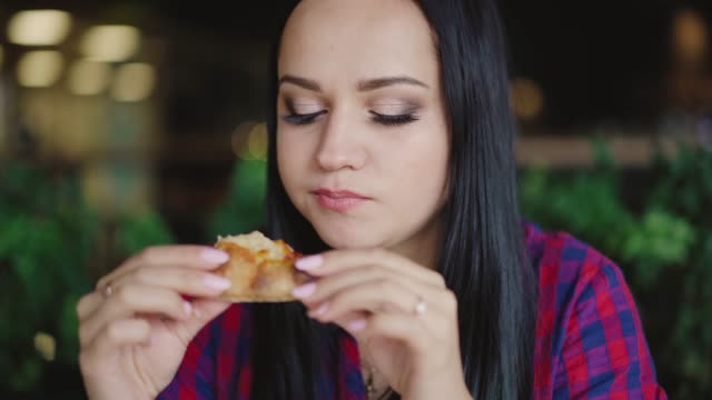beautiful brunette in a plaid shirt is eating pizza with enjoy in the cafe on the background of the interior video
