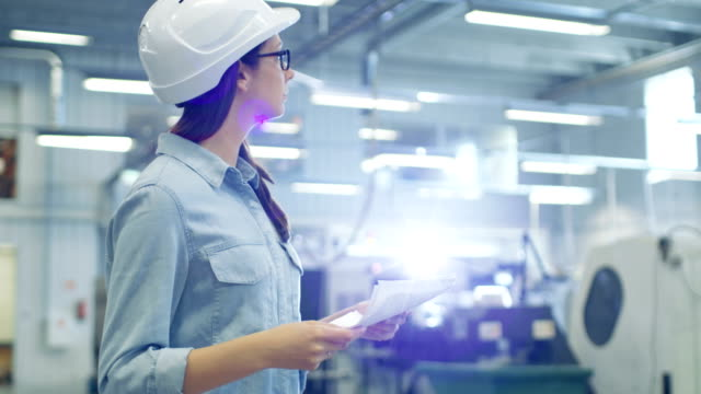 Beautiful Brunette Industrial Engineer Wearing Hard Hat Studies Blueprints and Documents while Walking Through Factory. video