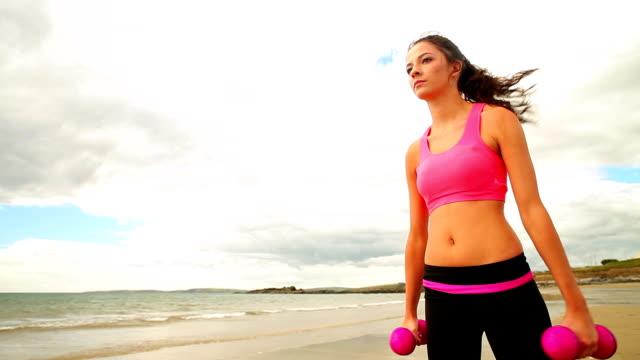 piękne brunette podnoszenia hantle na plaży - biustonosz sportowy filmów i materiałów b-roll