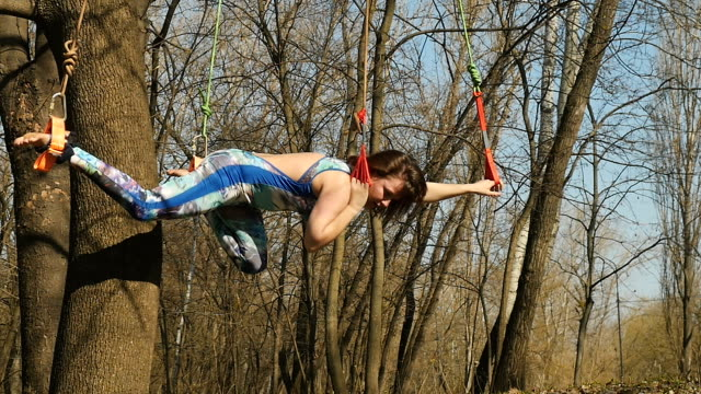 Beautiful brunette makes a stretching exercises on ropes in park Young woman practicing aerogravity in the park. The woman makes physical exercises on the ropes on tree. Flexible female hanging on the ropes and stretching her body and muscles. She's moving slowly and accuracy. arthropod stock videos & royalty-free footage
