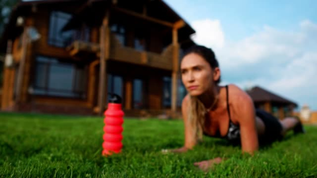 beautiful brunette on the background of a large mansion engaged in fitness and performs plank exercise for the press, training outdoors Fit girl doing plank exercise outdoor in the park warm summer day. Concept of endurance and motivation. bodyweight training stock videos & royalty-free footage