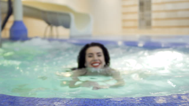 beautiful brunette swims in a blue pool - rossetto rosso video stock e b–roll