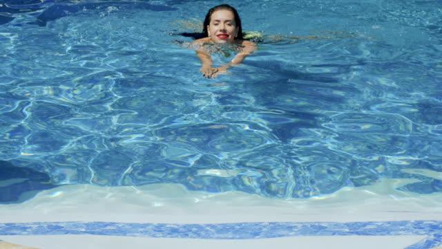vidéos et rushes de belle brune nage dans la piscine - rouge à lèvres rouge