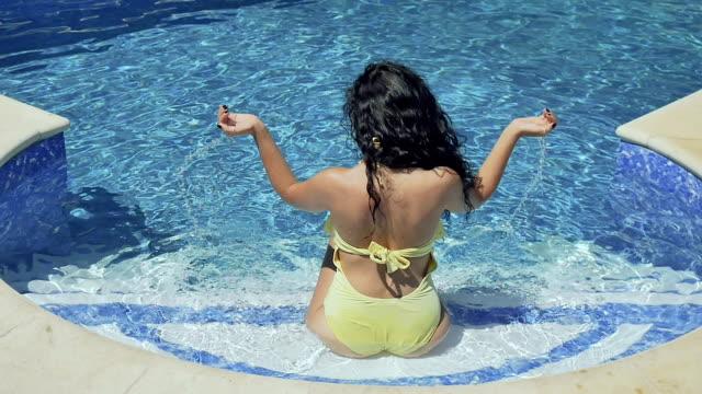 vidéos et rushes de belle brune prend l'eau dans les paumes et levez les mains, assis dans la piscine bleue - rouge à lèvres rouge