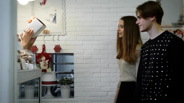 beautiful brunette wearing a light sweater and a black skirt and attractive young man with short hair happily take them white box with sweets inside, thanks to the pastry, and then go off to the side video