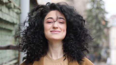piękna brunetka z fryzurą afro. uśmiecha się, śmieje się i pęka głowę - piękno filmów i materiałów b-roll