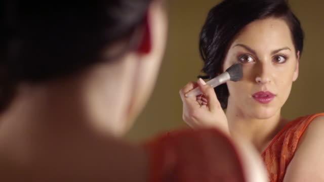 Beautiful brunette woman applying make-up video