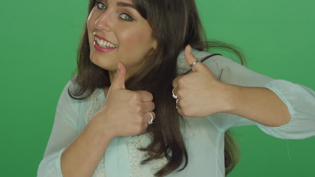 Beautiful brunette woman being silly and smiling, on a green screen studio background video