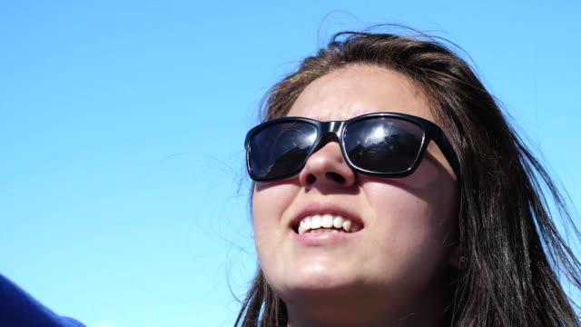 vidéos et rushes de belle femme brune à lunettes de soleil profiter de la lumière du soleil sur la slow motion. 1920 x 1080 - rouge à lèvres rouge