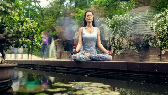 Beautiful brunette woman sitting in yoga pose in par Beautiful brunette woman sitting in yoga pose in park, while people passing by. Time lapse. Cinemagraph zen like stock videos & royalty-free footage