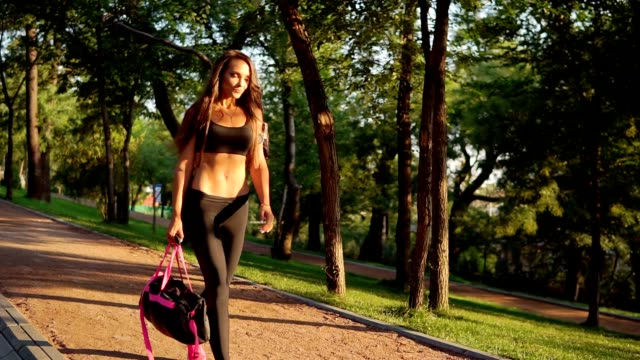 Beautiful brunette woman walking with sport bag in the park. Fit healthy sport woman exercising in the morning. Slowmotion shot video