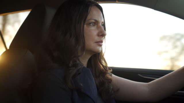 beautiful brunette woman with long hair driving car at sunset - brązowe włosy filmów i materiałów b-roll
