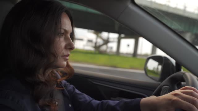 beautiful brunette woman with long hair driving car, view from passanger seat. - brązowe włosy filmów i materiałów b-roll