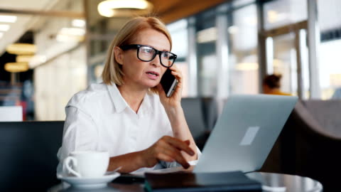 vídeos de stock e filmes b-roll de beautiful business lady talking on mobile phone and working with laptop in cafe - a usar um telefone