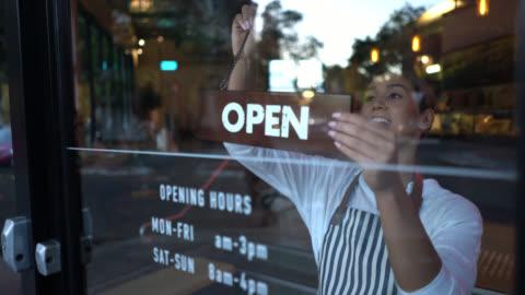 vídeos y material grabado en eventos de stock de hermosa empresaria de una panadería de colocación de la muestra abierta en la entrada mirando muy feliz - small business