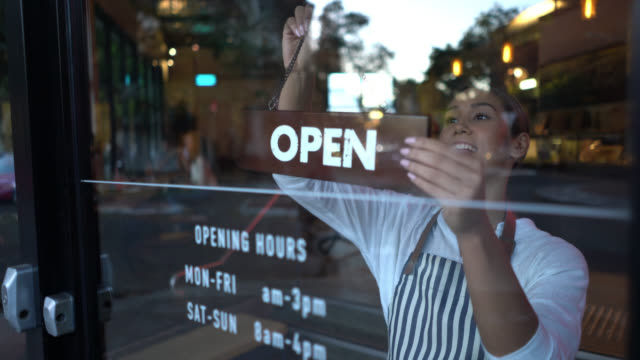 Beautiful business owner of a bakery putting up the open sign at the entrance looking very happy Beautiful business owner of a bakery putting up the open sign at the entrance looking very happy and smiling - Shot through window glass owner stock videos & royalty-free footage
