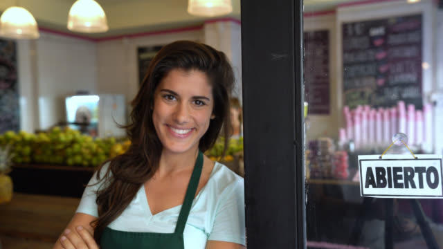 Beautiful business owner of a juice bar walking up to the entrance to put an open sign on the window and looking to the camera smiling - video